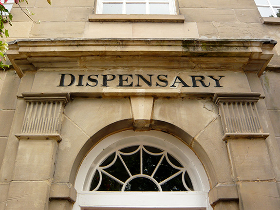 An old and weathered ornate stone building is seen focused close up on the wording 'Dispensary' set inline with the stone above a half-round white trimmed wooden window.